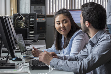 Asian female and Caucasian male working in an information technology office