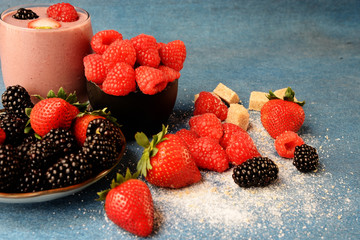 Delicious blackberry, raspberry and blueberry smoothie in glass and bowls with assorted fresh berries