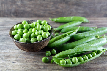 Green peas in wooden bowl on wood