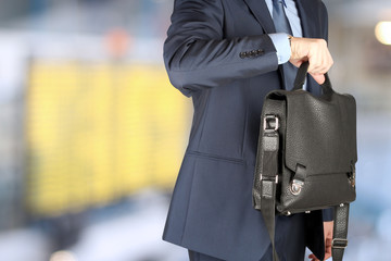 businessman  holding leather briefcase checking time on his wat