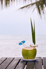 Coconut water drink served in coconut with drinking straw on the