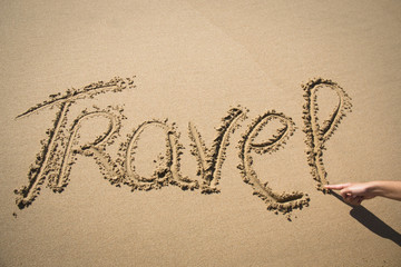 The word travel written in the sand on a beach in Mozambique