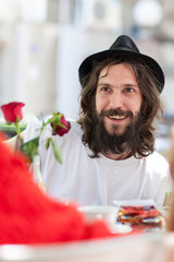 young man with hat and beard having fun at the bar