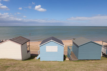 Row of pastel painted wooden beach huts.