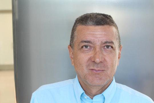 Portrait of mature middle eastern businessman smiling inside office building