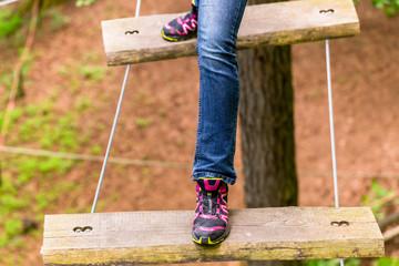 Mädchen macht Schritt auf Hängebrücke