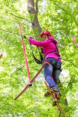 Frau im Klettergarten oder Hochseilpark