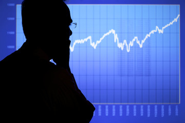 A man in silhouette is contemplating a rising financial or stock chart displayed on an LCD screen. Focus is on the man.