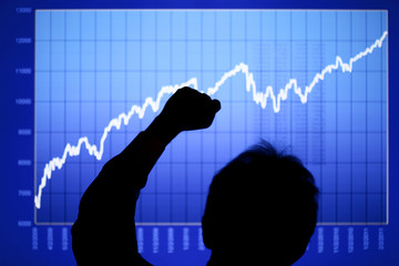Silhouette of a man giving a fist pump in front of a rising stock chart on an LCD display. Focus is on man's hand.