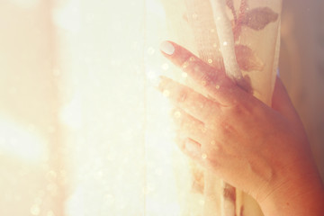 woman's hand opening curtains in a bedroom. natural light burst. filtered image