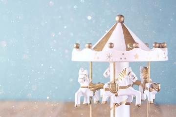 old vintage white carousel horses on wooden table