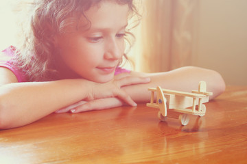 cute kid looking at old wooden airplane. selective focus