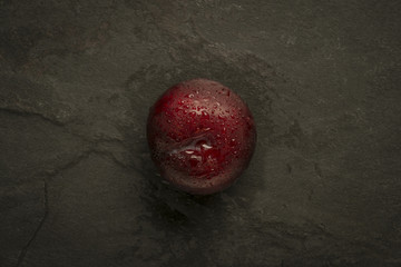Plum with water droplets on slate