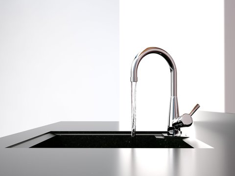 water flows from the kitchen tap to black kitchen sink