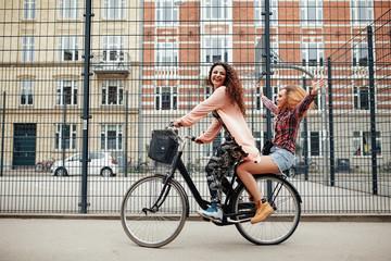 Two young women enjoying bike ride on city street