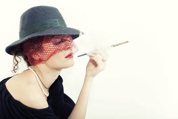 Young beautiful woman with cigarette in mouthpiece in hat with v