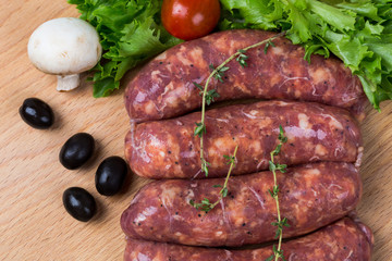 uncooked raw sausages on wooden board