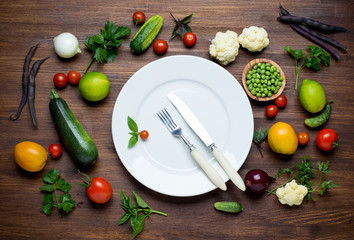 Photo of white plate and fresh vegetables. Top view