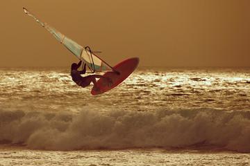 windsurfer jumping in a sunset sky
