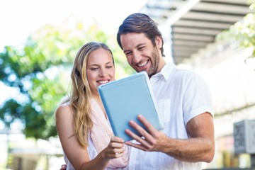 Smiling couple using tablet computer