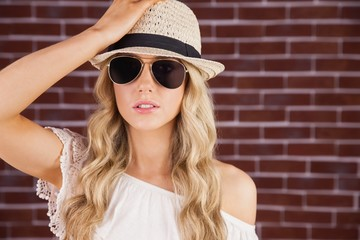 Gorgeous blonde hipster posing with straw hat