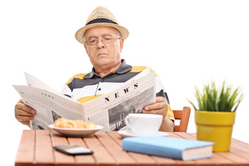 Mature man reading a newspaper seated at a coffee table