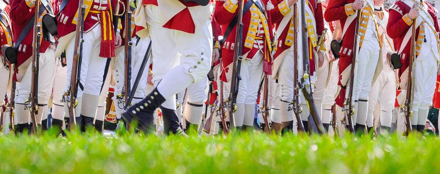 Legs of British soldiers of American revolutionary war on green battlefield in Lexington, MA