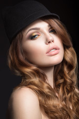 Beautiful girl with bright makeup and curls in a hat. Beauty face. Picture taken in the studio on a black background.