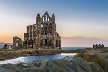Aluminium Prints Ruins Stone ruins of Whitby Abbey on the cliffs of Whitby, North Yorkshire, England at sunset.