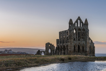 Deurstickers Rudnes Stone ruins of Whitby Abbey on the cliffs of Whitby, North Yorkshire, England at sunset.