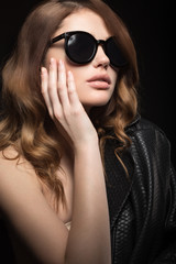 Beautiful girl in dark sunglasses, with curls and evening makeup. Beauty face. Picture taken in the studio on a black background.
