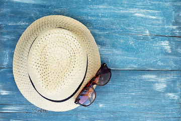 Hat, sunglasses isolated on blue wooden background