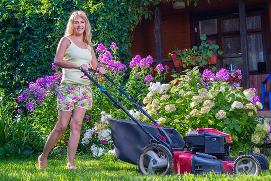 Женщина в саду косит траву