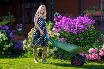 Женщина в саду с тачкой