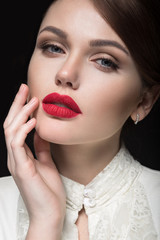 Beautiful girl with red lips in white clothes in the form of retro. Beauty face. Picture taken in the studio on a black background.