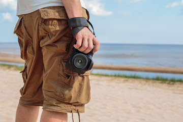 Traveler admires the view of the sea, holding the camera at the ready