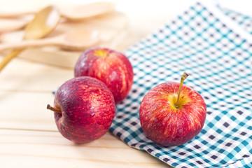 Three fresh apples on wooden background