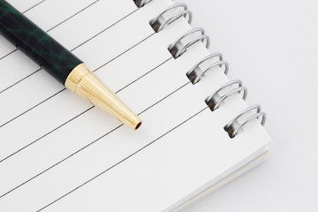 Close-up of a lined paper spiral bound notebook with a ballpoint pen on a white background.