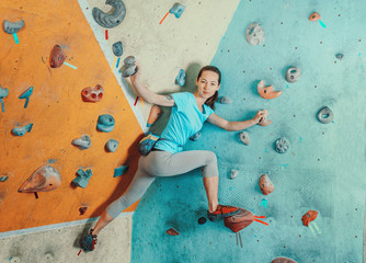 Sporty woman standing on artificial boulders