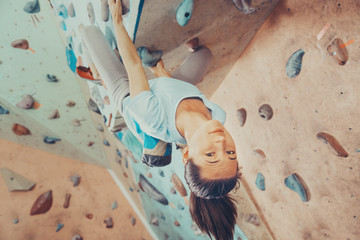 Smiling young woman climbing indoor