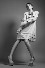 Girl in stylish clothes. Beauty, fashion, original poses. Picture taken in a studio full-length. Black and white photo
