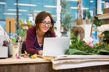 Happy Florist Using Laptop At Counter In Flower Shop