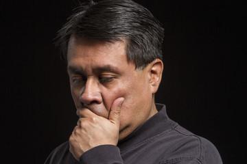 Studio portrait of a stressed Hispanic male