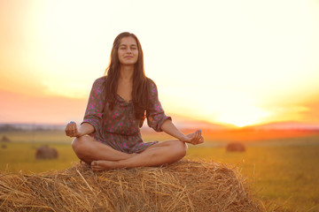 Beautiful girl in the Lotus position in a field at sunset