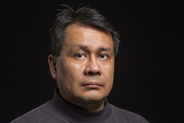 Studio portrait of a serious Hispanic man