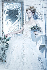 Beautiful girl, white dress in image of the Snow Queen with a crown on her head.