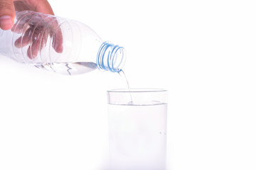Pouring water from bottle into glass on white background.