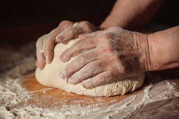 Senior woman hands knead dough on a table in her home kitchen