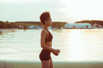 Attractive young African girl athlete running at sunset along the beach. Fitness training of runner.