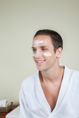 Smiling man with cream on her face